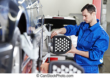 auto mechanic at wheel alignment work with sensor - car...