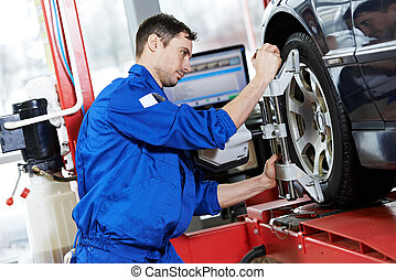 car mechanic installing sensor during suspension adjustment and automobile wheel alignment work at repair service station