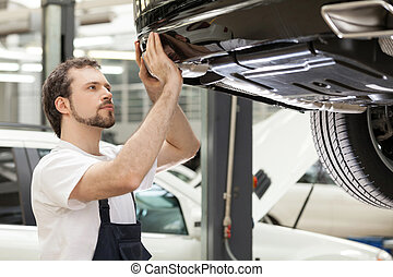 Auto mechanic at work. Confident mechanic working at the repair shop
