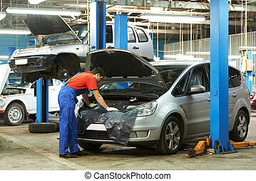 auto mechanic at work - One young auto mechanic examining ...