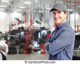 Auto repair service. Handsome smiling mechanic.