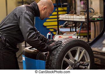 auto mechanic balancing car wheel at workshop - car service,...