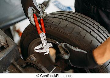 Auto mechanic balancing wheel, tire service
