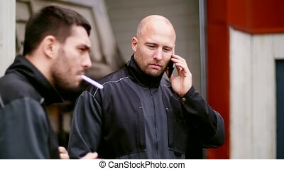 auto mechanic calling on smartphone at brake - car service...