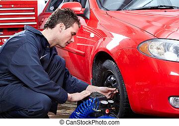 Auto mechanic changing a tire.