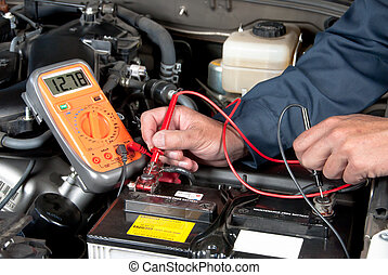 An auto mechanic uses a multimeter voltmeter to check the voltage level in a car battery.