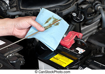 Auto Mechanic Checking Oil - An auto mechanic checks the oil...