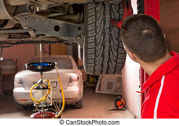 Auto mechanic checking the suspension on a car