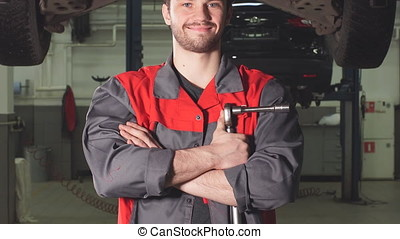 Auto mechanic crossed hands and looking at camera while...