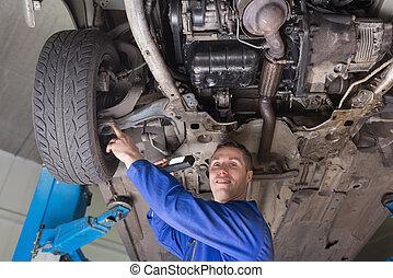 Auto mechanic examining car tire