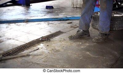 auto mechanic guy work on car brake system. tilt up.