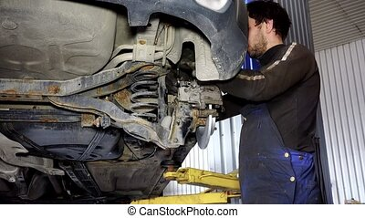 auto mechanic guy working on car brake system.