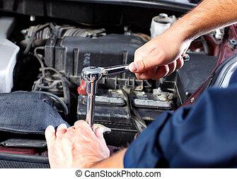 Hands of mechanic working in auto repair shop.