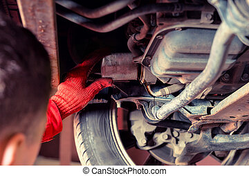 Auto mechanic in uniform working underneath a lifted car