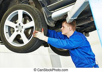 auto mechanic inspecting car wheel