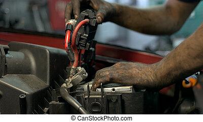 Auto mechanic installing accumulator battery.