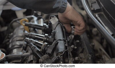 Auto Mechanic is Working on Engine in Car Repair Shop.