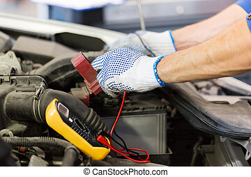 auto mechanic man with multimeter testing battery