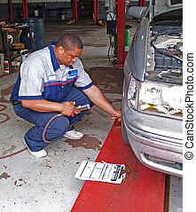 Auto Mechanic Performing Tire Press - Auto mechanic...
