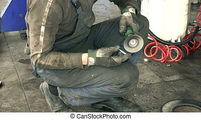 Auto mechanic polish rusty bolts with electric grinder tool near lifted car