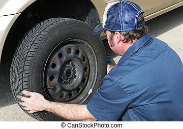 Auto Mechanic Removing Tire