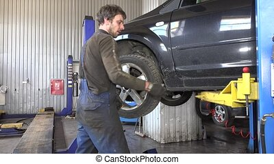 Auto mechanic removing wheel from car in garage.