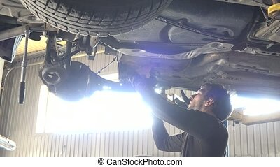 auto mechanic repairing automobile against intensive window...