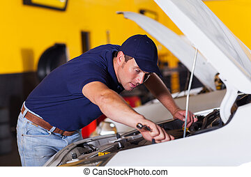 auto mechanic repairing vehicle inside workshop