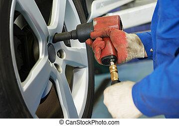 auto mechanic screwing car wheel