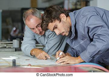 auto mechanic shows trainee how to work