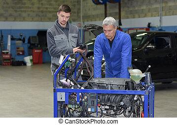 auto mechanic shows trainee maintenance of car engine