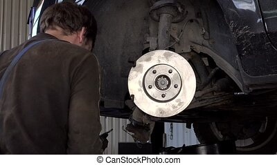 Auto mechanic strengthen car brake discs and pads in garage.