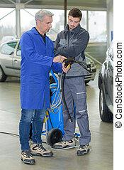 auto mechanic teacher shows the trainee maintenance of the car