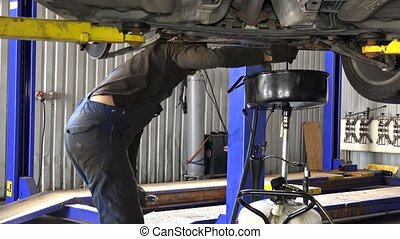 auto mechanic technician replacing and changing motor oil in...