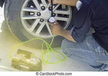 Auto mechanic uses a Car Tire Pressure Check in the Auto Service Garage.