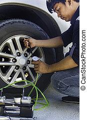 Auto mechanic uses a Car Tire Pressure Check.