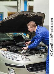 Auto mechanic with laptop repairing car