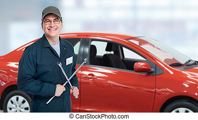 Auto mechanic with tire wrench in garage.