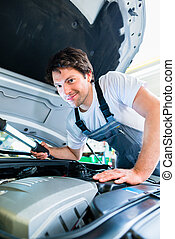 Auto mechanic working in car service workshop