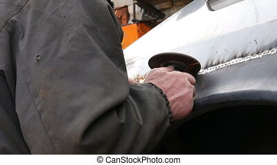 Auto mechanic working on a car body in garage