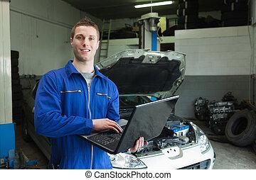 Auto mechanic working on laptop
