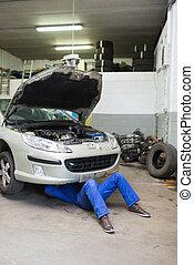 Auto mechanic working under car