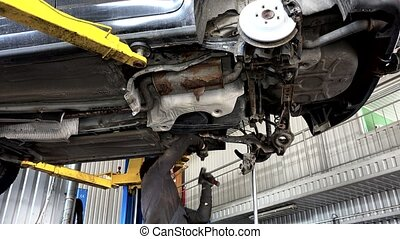 auto mechanic working with hammer under automobile in car repair service shop