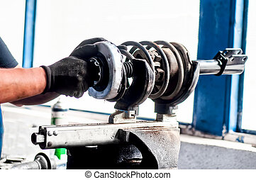 Auto mechanical engineer adjusting a car shock absorber in car