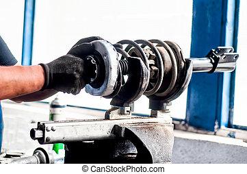 Auto mechanical engineer adjusting a car shock absorber in car service workshop