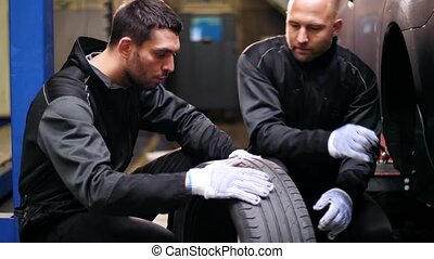 auto mechanics repairing car tire with blowout - car...