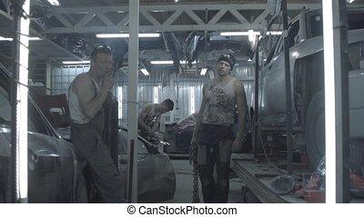 Auto mechanics team at work in garage in slow motion