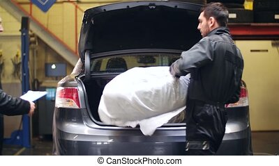 auto mechanics with car tire at workshop - car service,...