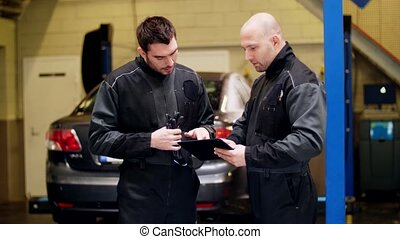 auto mechanics with tablet pc talking at car shop - auto...