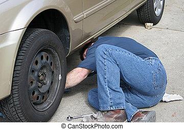 Auto Repair - A mechanic reaching under a car.